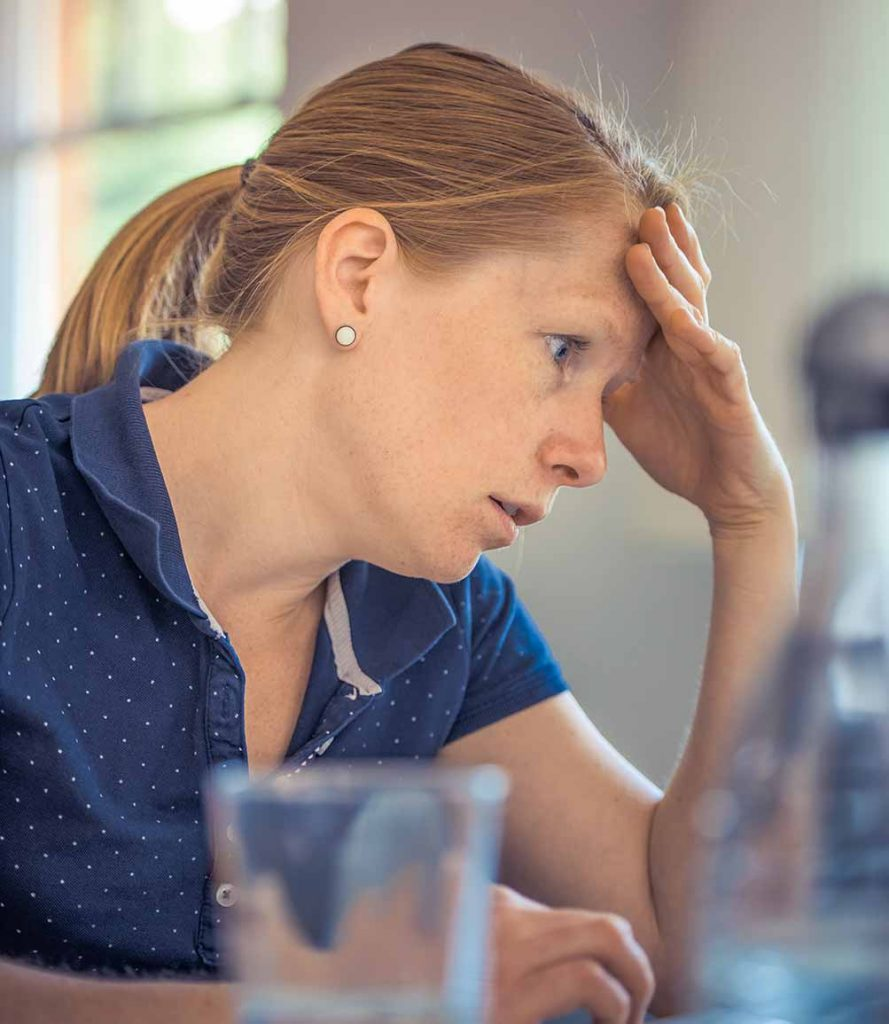 a young woman looks very stressed while on her computer