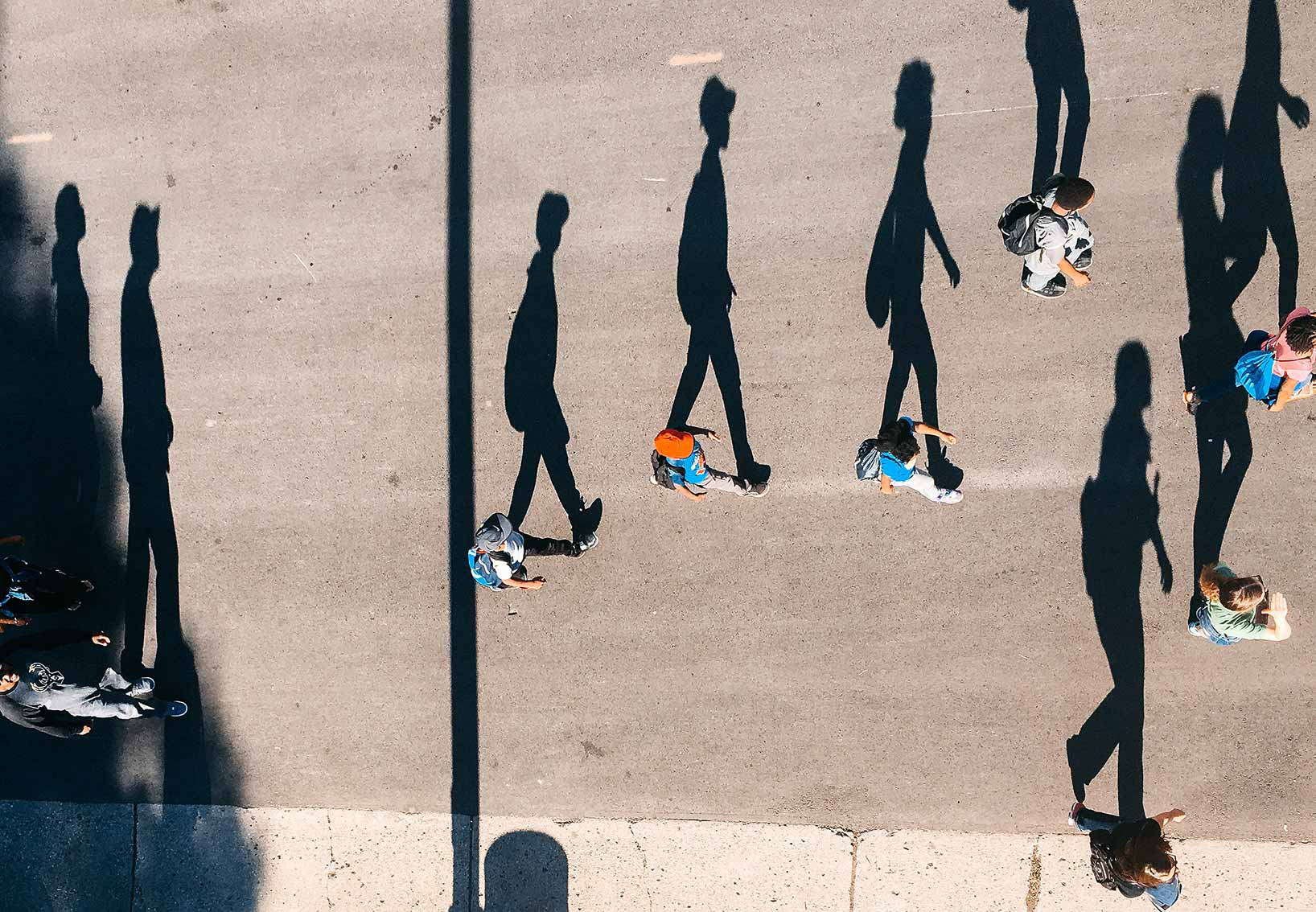 a bunch of pedestrians are pictured from above crossing a street