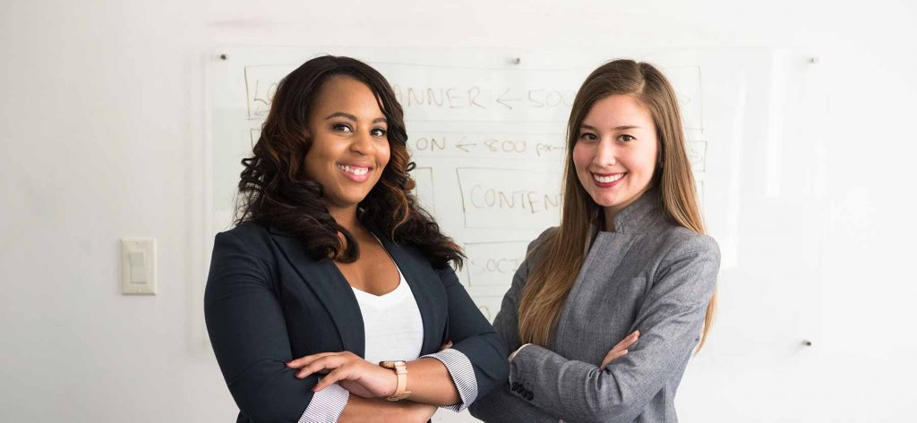 two professionally dressed women stand together in front of a white board