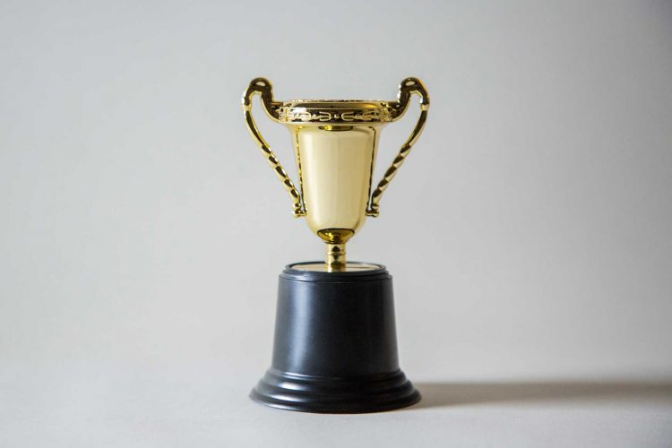 a gold trophy with a white background